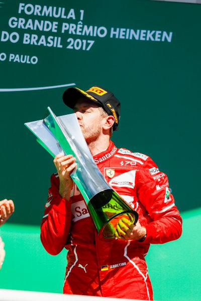 Interlagos, Sao Paulo, Brazil. Sunday 12 November 2017. Sebastian Vettel, Ferrari, 1st Position, kisses his trophy on the podium. World Copyright: Glenn Dunbar/LAT Images  ref: Digital Image _X4I3727