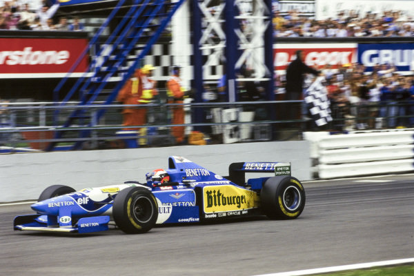 Johnny Herbert, Benetton B195 Renault, celebrates as he crosses the finish line and takes the chequered flag.