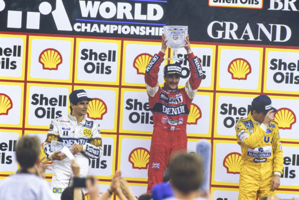 Nigel Mansell, 1st position, Nelson Piquet, 2nd position, and Ayrton Senna, 3rd position, on the podium.