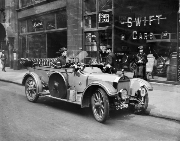 A Voluntary Aid Detachment worker waits in her Swift for her next assignment, outside the Swift Cars showroom.
