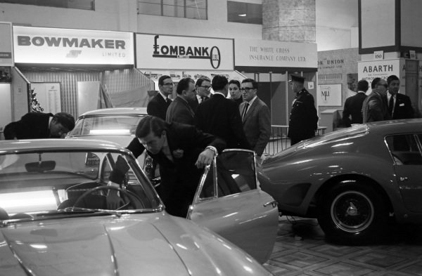 Peter Sellers talks with others standing next to a Ferrari 250 GTO.