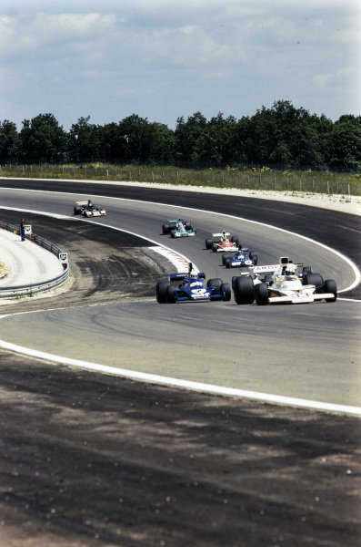 Mike Hailwood, McLaren M23 Ford, leads Jody Scheckter, Tyrrell 007 Ford, Carlos Reutemann, Brabham BT44 Ford, Jacky Ickx, Lotus 72E Ford, Patrick Depailler, Tyrrell 006 Ford, Emerson Fittipaldi, McLaren M23, and Jean-Pierre Beltoise, BRM P201.