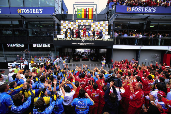 Michael Schumacher, 1st position, Rubens Barrichello, 2nd position, Fernando Alonso, 3rd position, and Jean Todt on the podium above the Ferrari and Renault teams.