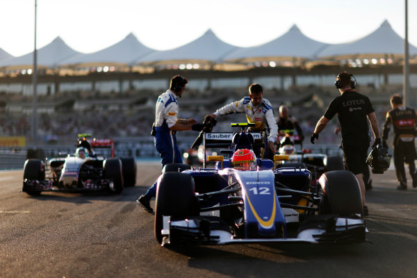 Yas Marina Circuit, Abu Dhabi, United Arab Emirates. Sunday 29 November 2015. Felipe Nasr, Sauber C34 Ferrari, and Carlos Sainz Jr, Toro Rosso STR10 Renault, arrive on the grid. World Copyright: Charles Coates/LAT Photographic ref: Digital Image _99O1702