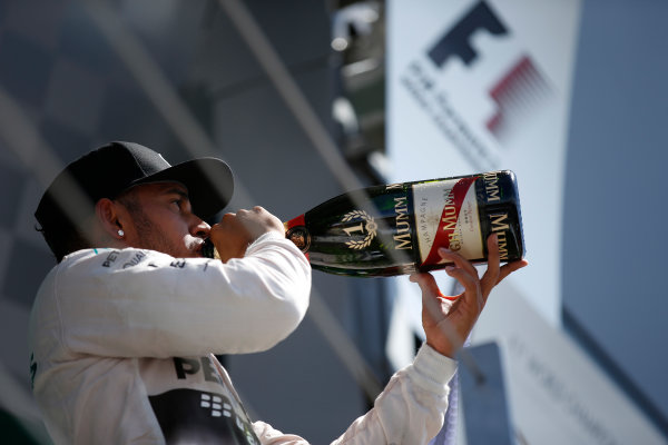 Silverstone Circuit, Northamptonshire, England. Sunday 5 July 2015. Lewis Hamilton, Mercedes AMG, 1st Position, tastes the victory Champagne on the podium. World Copyright: Glenn Dunbar/LAT Photographic ref: Digital Image _89P4150