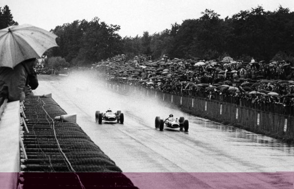 1966 German Grand Prix.Nurburgring, Germany. 7 August 1966.Graham Hill, BRM P261, 4th position, and Denny Hulme, Brabham BT20-Repco, retired, in the rain, action.World Copyright: LAT PhotographicRef: Autosport b&w print