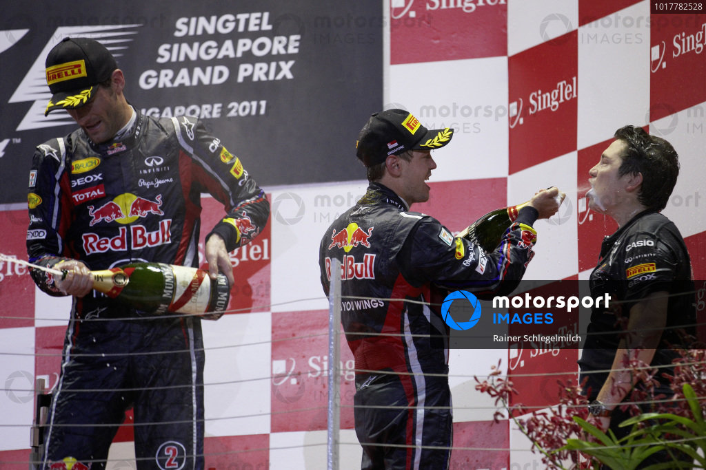 Sebastian Vettel, 1st position, gives a champagne shower to Red Bull Racing performance engineer Tim Malyon during the podium ceremony, alongside Mark Webber, 2nd position.