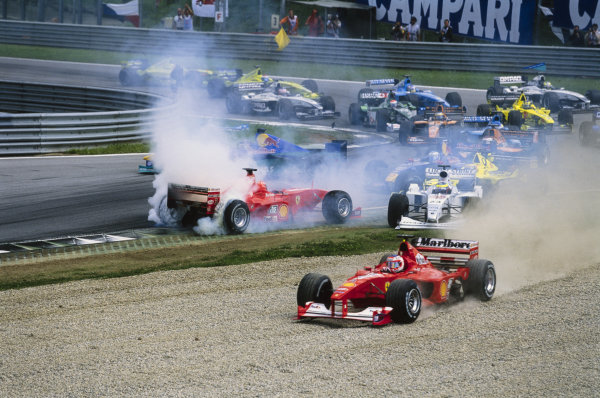 Rubens Barrichello, Ferrari F1-2000, runs into a gravel trap, as Michael Schumacher, Ferrari F1-2000, spins in front of Riccardo Zonta, BAR 002 Honda