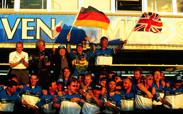1995 Pacific Grand Prix.Tanaka International, Aida, Japan.20-22 October 1995.Michael Schumacher celebrates with Flavio Briatore, Luciano Benetton and rest of the Benetton-Renault team after clinching the World Drivers and Constructors Championships.  Ref: 95PAC19. World - LAT Photographic