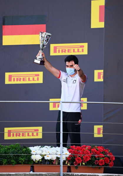 A member of the Hitech Grand Prix team on the podium