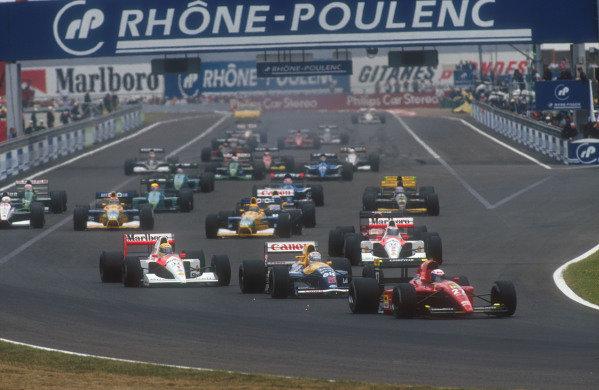 1991 French Grand Prix.Magny-Cours, France.5-7 July 1991.Alain Prost (Ferrari 643) leads Nigel Mansell (Williams FW14 Renault), Ayrton Senna, Gerhard Berger (both McLaren MP4/6 Honda's), Jean Alesi (Ferrari 643), Roberto Moreno, Nelson Piquet (both Benetton B191 Ford's) and Stefano Modena (Tyrrell 020 Honda) at the start.Ref-91 FRA 06.World Copyright - LAT Photographic