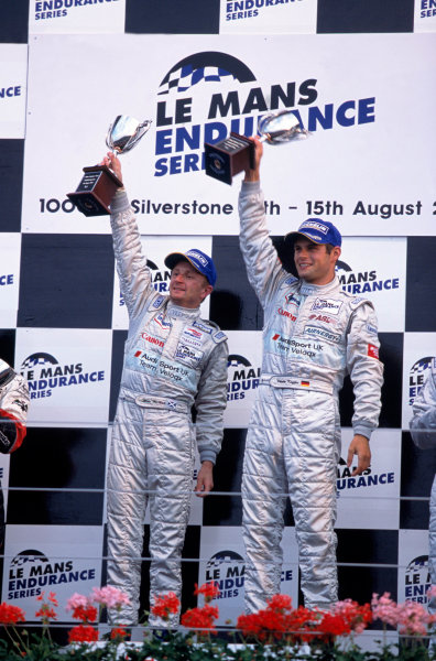 2004 Le Mans Endurance SeriesSilverstone 1000 KilometersSilverstone, England. 12th - 14th August 2004Allan McNish and Pierre Kaffer (Veloqx Audi R8) show off their winner's trophies on the podium.World Copyright: Glenn Dunbar/LAT Photographicref: 35mm Transparency A09