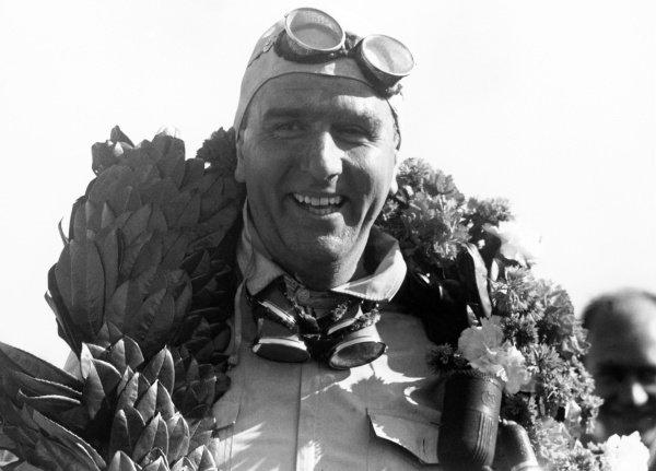 Giuseppe 'Nino' Farina, 1st position, celebrates winning the first Formula 1 World Championship race.