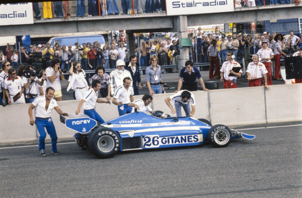 Jacques Laffite, Ligier JS7 Matra is greeted by his team on the main straight as he claims their first victory.