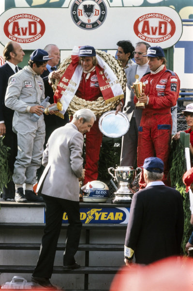 James Hunt celebrates victory on the podium with, Jody Scheckter, 2nd position and Jochen Mass, 3rd position.