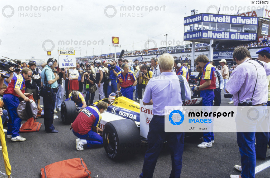 Nigel Mansell, Williams FW11B Honda, on the grid. Barrie Gill stands with microphone in hand.