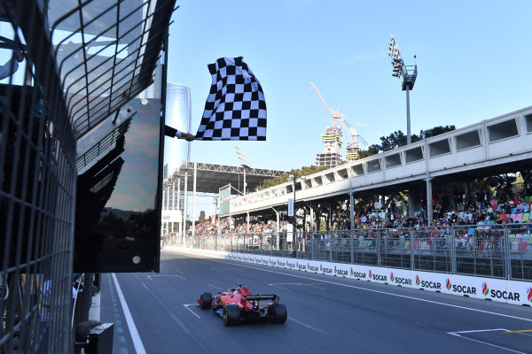 The chequered flag is waved at the end of the race as Sebastian Vettel, Ferrari SF90, 3rd position, passes