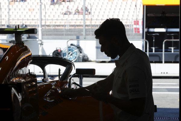 A mechanic works on the Stoffel Vandoorne McLaren MCL33 Renault in the team's garage.