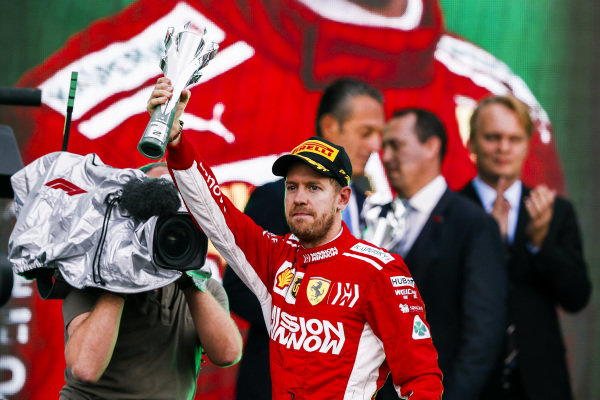 Sebastian Vettel, Ferrari, 2nd position, lifts his trophy on the podium