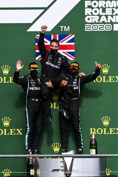Valtteri Bottas, Mercedes-AMG Petronas F1, 2nd position, and Lewis Hamilton, Mercedes-AMG Petronas F1, 1st position, lift their team mate into the air on the podium