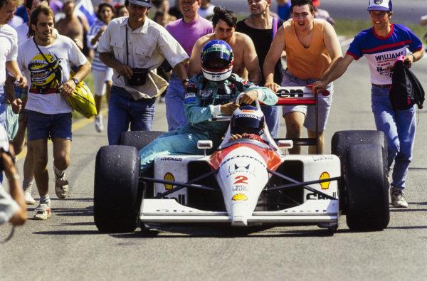 Gerhard Berger, McLaren MP4-6 Honda, gives Ivan Capelli a lift. Fans surround the car.