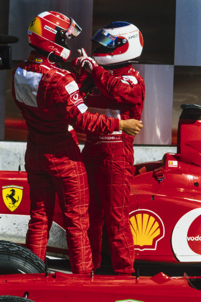 Michael Schumacher and Rubens Barrichello embrace in Parc Ferme.
