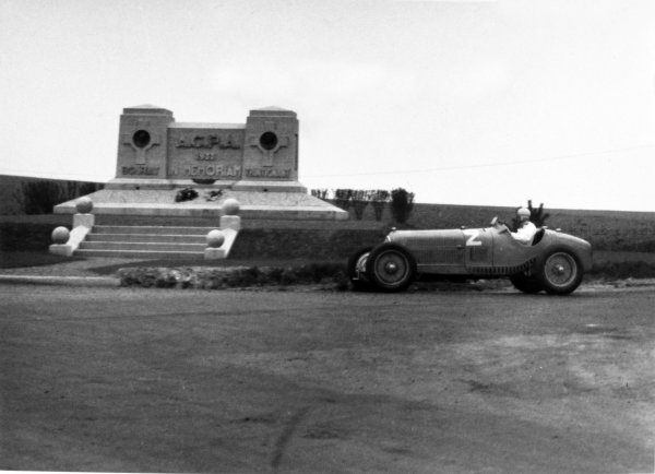 """1935 Picardie Grand Prix Peronne, France. 26 May 1935 Raymond Sommer, Alfa Romeo Tipo-B """"P3"""", 3rd position, passes the memorial to Louis Trintignant (father of Maurice) and Guy Bouriat at Mons-en-Chaussee, where both had been killed in 1933. Action World Copyright: Robert Fellowes/LAT PhotographicRef: 35PIC04"""