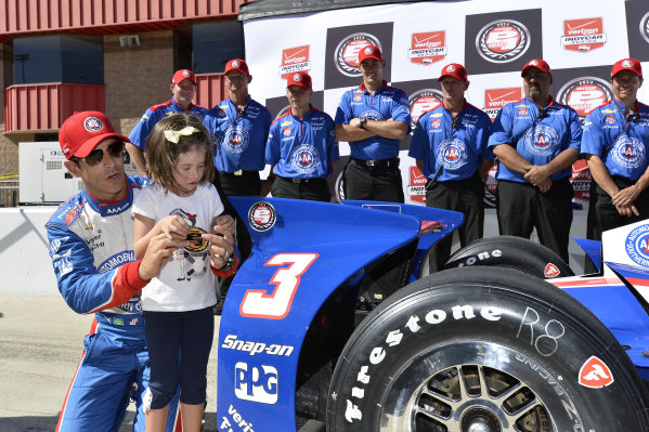 Helio Castroneves (BRA) Team Penske celebrates pole position with his team and daughter.
