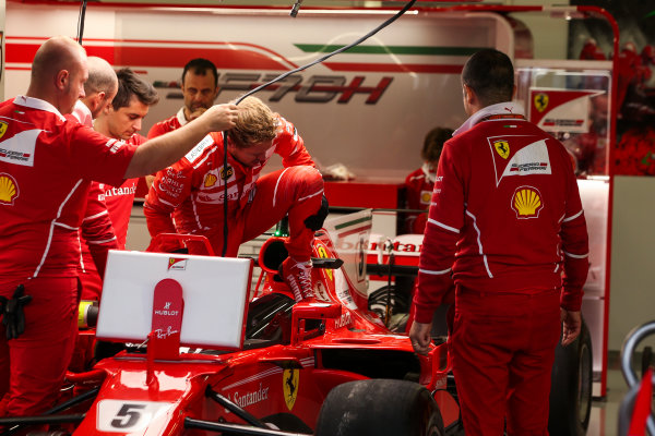 Silverstone, Northamptonshire, UK.  Thursday 13 July 2017. Sebastian Vettel, Ferrari SF70H, climbs into his car in the garage. World Copyright: Charles Coates/LAT Images  ref: Digital Image AN7T2200