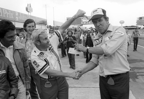 (L to R): Teddy Mayer (USA) McLaren Team Owner hands over a cheque to Ken Tyrrell (GBR) Tyrrell Team Owner after losing a pit stop tyre change competition. British Grand Prix, Rd 9, Silverstone, England, 19 July 1975.