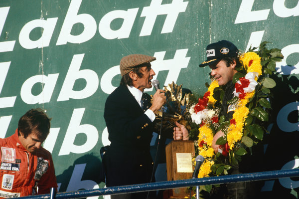 1980 Canadian Grand Prix.  Montreal, Canada. 26-28th September 1980.  Alan Jones, Williams, 1st position, interviewed on the podium by Jackie Stewart, with Carlos Reutemann, Williams, 2nd position.  Ref: 80CAN03. World Copyright: LAT Photographic