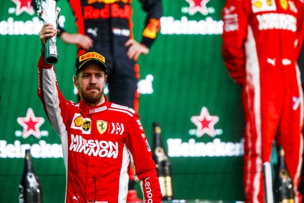 Sebastian Vettel, Ferrari, 2nd position, holds up his trophy on the podium
