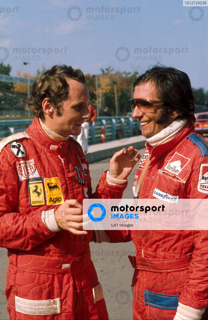 1975 United States Grand Prix. Watkins Glen, New York, USA. 3-5 October 1975. Niki Lauda (Ferrari) 1st position and new drivers world champion chats with the outgoing champion, Emerson Fittipaldi (McLaren Ford) 2nd position. Ref-75 USA 10. World Copyright - LAT Photographic