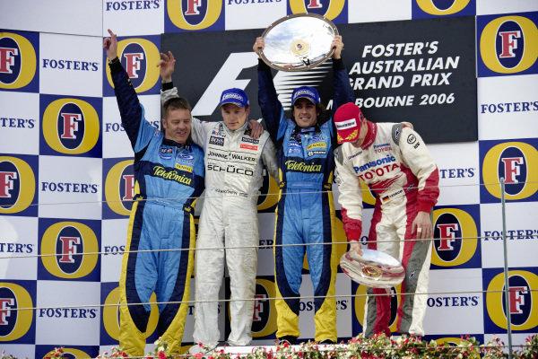 Fernando Alonso celebrates victory on the podium with race engineer Rod Nelson, Kimi Räikkönen, 2nd position, and Ralf Schumacher, 3rd position.