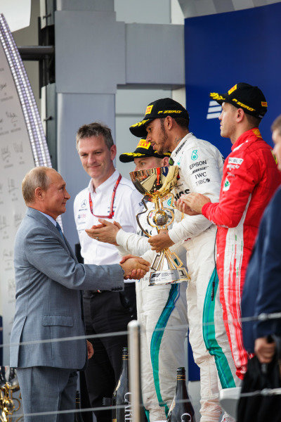 Valtteri Bottas, Mercedes AMG F1, 2nd position, and Sebastian Vettel, Ferrari, 3rd position, applaud as Lewis Hamilton, Mercedes AMG F1, 1st position, receives his trophy from Vladimir Putin, President of Russia