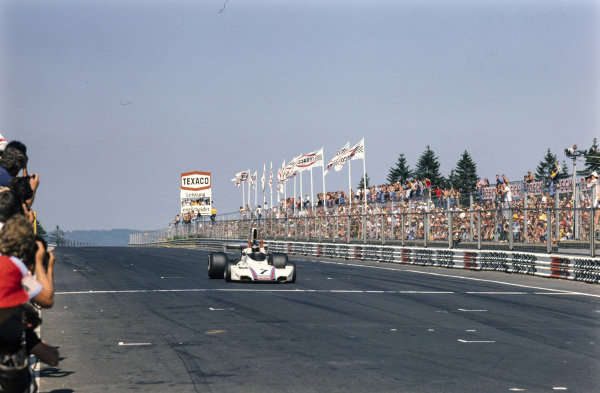 Carlos Reutemann, Brabham BT44B Ford throws his arms in the air to celebrate victory as he crosses the finish line.