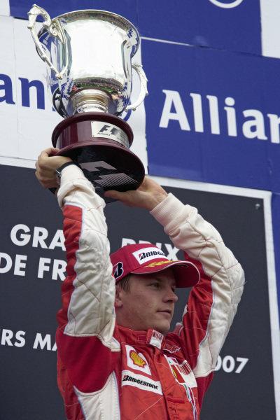 Kimi Raikkonen raises his winner's trophy on the podium.