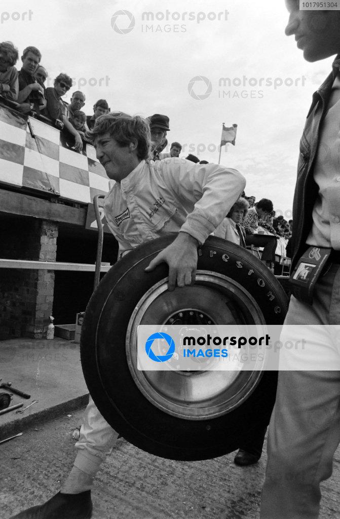 Jochen Rindt carries a Firestone tyre through the pit lane.