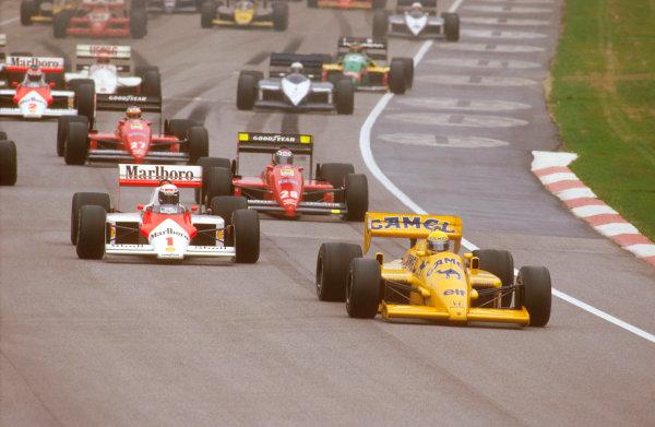Imola, Italy.1-3 May 1987.Ayrton Senna (Lotus 99T Honda) leads Alain Prost (McLaren MP4/3 TAG Porsche) and Gerhard Berger (Ferrari 187) at the start.Ref-87 SM 12.World Copyright - LAT Photographic
