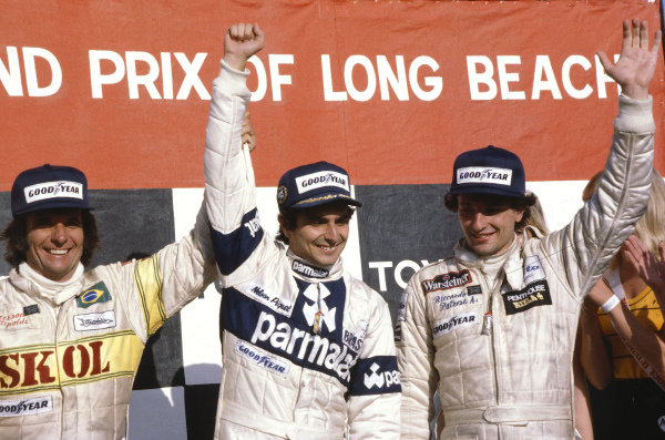 1980 United States Grand Prix West.Long Beach, California, USA.28-30 March 1980.Nelson Piquet (Brabham Ford) celebrates 1st position on the podium with Riccardo Patrese (Arrows Ford) 2nd position and Emerson Fittipaldi (Fittipaldi Ford) 3rd position.Ref-80 LB 14.World Copyright - LAT Photographic