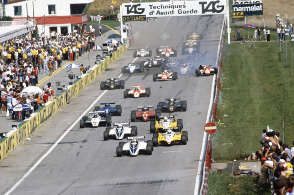 Nelson Piquet, Brabham BT50 BMW, leads Alain Prost, Renault RE30B, Riccardo Patrese, Brabham BT50 BMW, René Arnoux, Renault RE30B, Keke Rosberg, Williams FW08 Ford, and Patrick Tambay, Ferrari 126C2, at the start. In the background, Bruno Giacomelli, Alfa Romeo 182, crashes into the barrier.