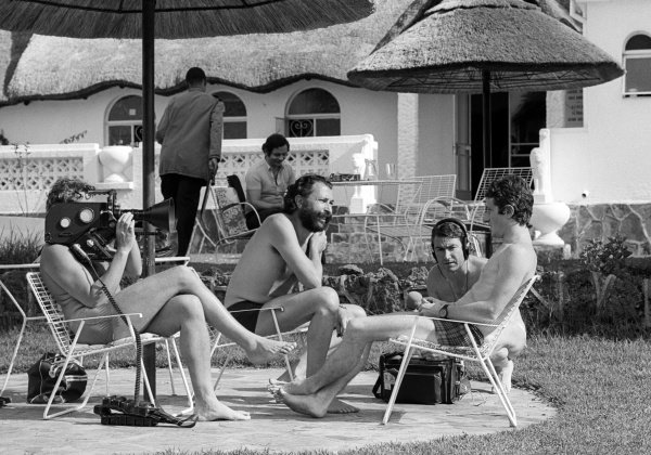 Patrick Depailler (FRA) Tyrrell (Right), is interviewed by a film crew whilst staying at the Kyalami Ranch Hotel. South African Grand Prix, Rd2, Kyalami, South Africa, 6 March 1976.