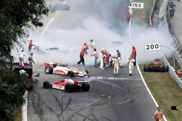 The immediate aftermath of the multi-car accident at the start of the race: Ronnie Peterson (SWE) Lotus (Yellow overalls) lies in the track having been pulled from his shattered, burning, Lotus 78, and is tended to by marshals, Clay Regazzoni (SUI) Shadow (Red Overalls) and Patrick Depailler (FRA) Tyrrell (Blue helmet). James Hunt (GBR) McLaren (Black helmet) walks from the scene with team mate Bruno Giacomelli (ITA) McLaren. Vittorio Brambilla (ITA) (Right) lies - head slumped -in his Surtees TS20 after suffering a serious head injury from which he fully recovered. Tragically, Peterson would die from a blood clot following an operation in hospital on his badly broken legs.