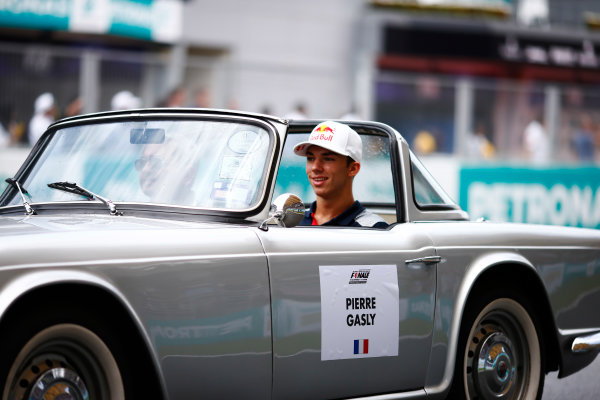 Sepang International Circuit, Sepang, Malaysia. Sunday 01 October 2017. Pierre Gasly, Reserve Driver, Toro Rosso, rides in a Triumph TR on the drivers' parade. World Copyright: Andy Hone/LAT Images  ref: Digital Image _ONZ0133
