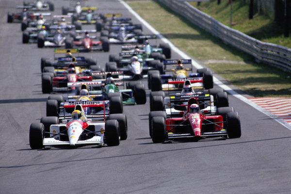 Ayrton Senna, McLaren MP4-6 Honda, and Alain Prost, Ferrari 643, lead the field into the first corner at the start.