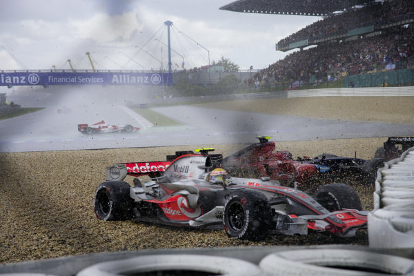 Lewis Hamilton, McLaren MP4-22 Mercedes and Scott Speed, Toro Rosso STR2 Ferrari slide into the gravel trap in the wet conditions as Anthony Davidson, Super Aguri SA07 Honda drifts around the hairpin on the slippery track.