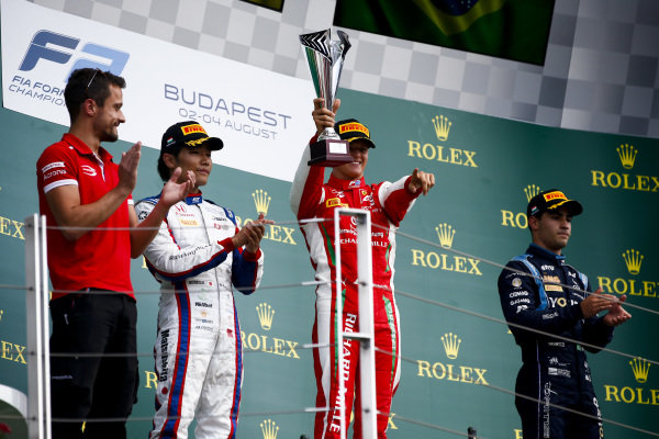HUNGARORING, HUNGARY - AUGUST 04: Nobuharu Matsushita (JPN, CARLIN), Race winner Mick Schumacher (DEU, PREMA RACING) and Sergio Sette Camara (BRA, DAMS) celebrate on the podium during the Hungaroring at Hungaroring on August 04, 2019 in Hungaroring, Hungary. (Photo by Andy Hone / LAT Images / FIA F2 Championship)