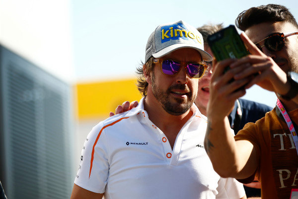 A fan takes a photo of Fernando Alonso, McLaren.
