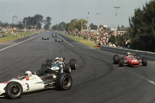 Mexico City, Mexico. 20 - 22 October 1967.  Denny Hulme (Brabham BT24 Repco) passes Bruce McLaren (McLaren M5A BRM) as they follow John Surtees (Honda RA300) into the hairpin.  Ref: 67MEX05. World Copyright: LAT Photographic
