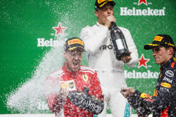 Valtteri Bottas, Mercedes AMG F1, 2nd position, Sebastian Vettel, Ferrari, 1st position, and Max Verstappen, Red Bull Racing, 3rd position, celebrate with Champagne on the podium.